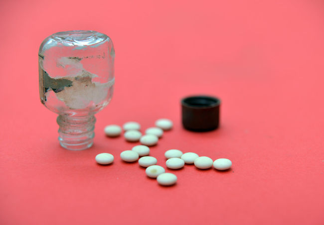 old bottle with unknown pills Healthcare Medicine Pouring Red Unknown Cap Capsule Close-up Danger Day Dirty Healthy Eating Indoors  Medical No People Old Bottle Pill In Bottle Small Bottle Studio Shot Tablette