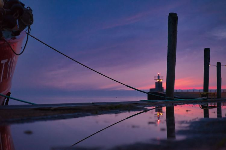 Reflection of wooden post in lake at sunset