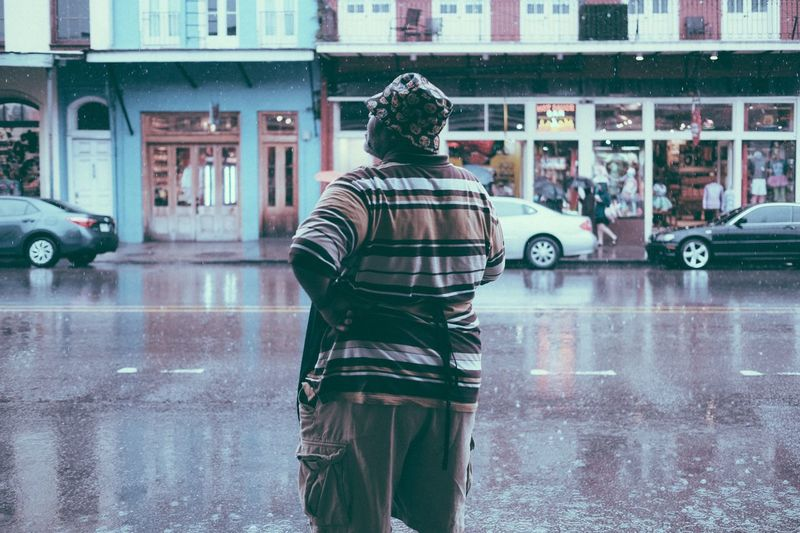 Rear View Of Man With Hand On Hip Standing On Footpath During Rainfall