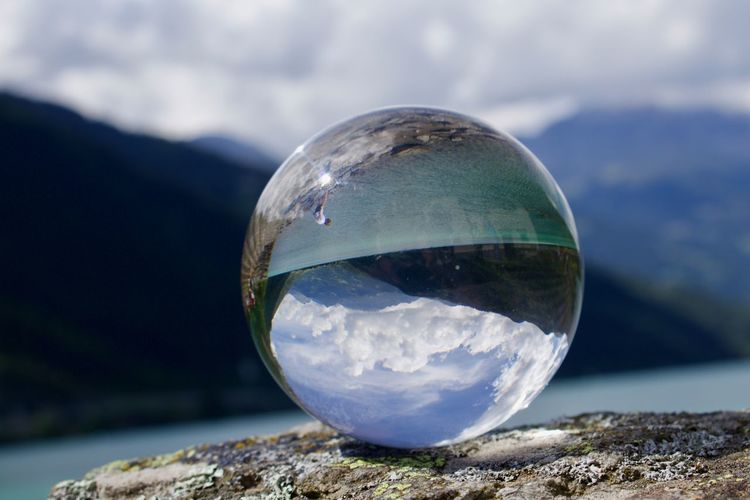 Close-up of crystal ball on rock against mountain