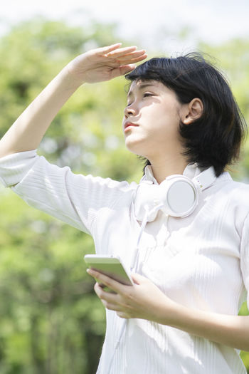 One Person Young Adult Wireless Technology Technology Mobile Phone Focus On Foreground Holding Leisure Activity Waist Up Communication Connection Day Hair Standing Adult Looking Telephone Young Women Lifestyles Human Arm Hairstyle Outdoors Arms Raised