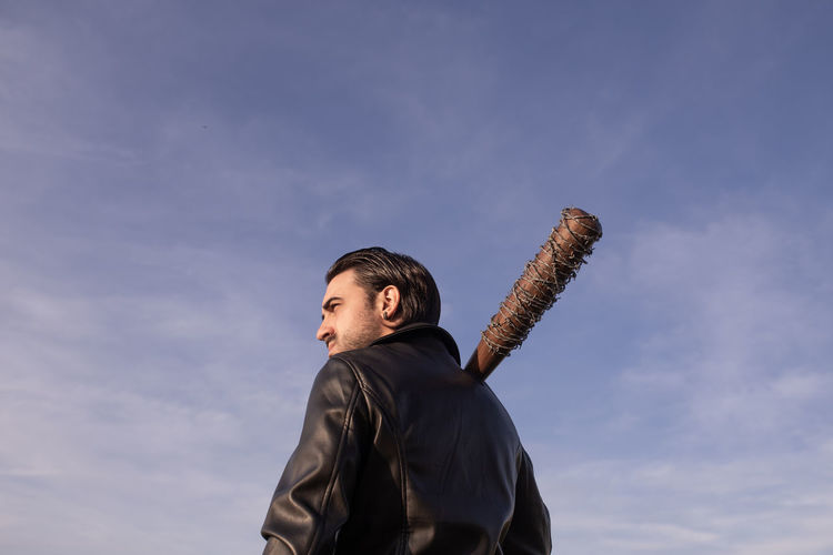 Mid adult man with barbed wire wrapped baseball bat looking away against sky