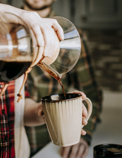 Close-up of hand pouring coffee in cup