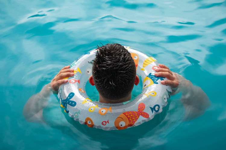 High angle view of man swimming in pool with inflatable