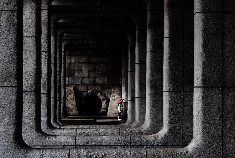 Girl standing in corridor along pillars
