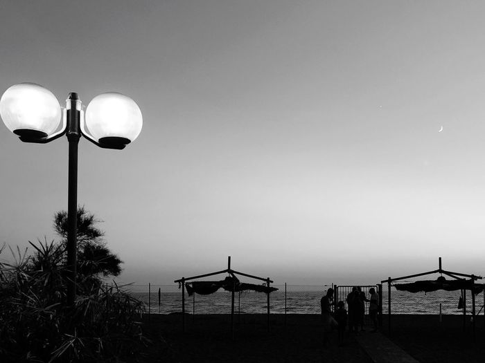 View Of Street Lights On Beach Against Clear Sky At Dusk