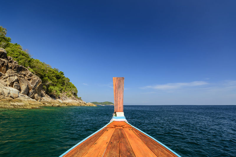 Beauty In Nature Blue Clear Sky Cliff Day Horizon Over Water Longtail Boat Mode Of Transport Nature Nautical Vessel No People Outdoors Rock - Object Scenics Sea Sky Transportation Water Wood - Material
