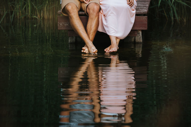 Low section of couple sitting by lake