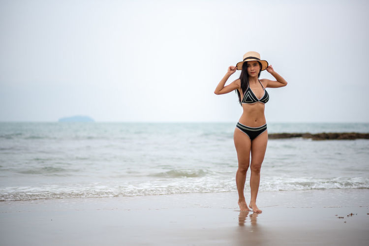 Sea Land Young Adult Young Women Water Clothing Beach One Person Beauty Full Length Lifestyles Real People Women Hat Standing Leisure Activity Beautiful Woman Beauty In Nature Bikini Horizon Over Water Sun Hat Hair Fashion Hairstyle