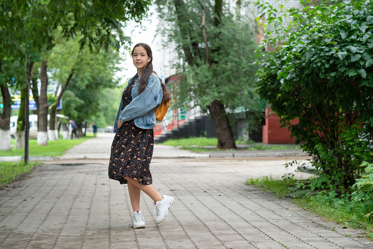 Full length portrait of young woman standing on footpath