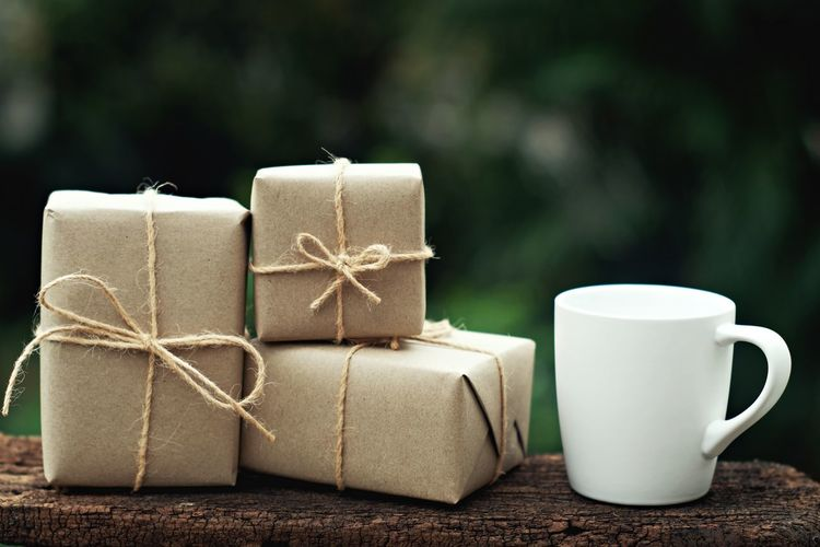 Close-up of gift boxes and coffee cup on wood