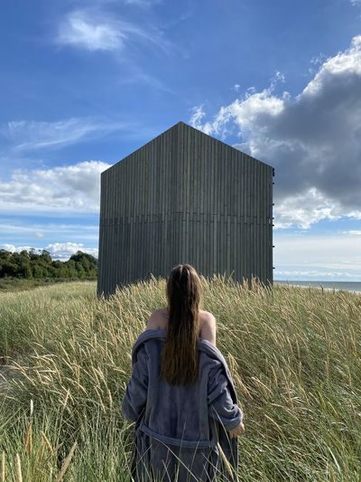 Rear view of woman standing on field against built structure
