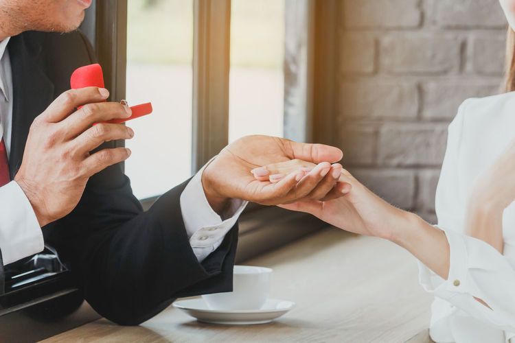 Close-Up Of Couple With Wedding Ring At Table