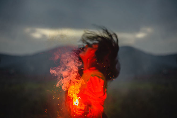 Young woman with fire crackers against sky
