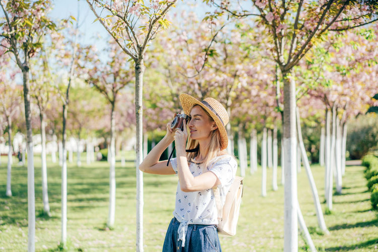 Close-up of woman photographing while standing against trees