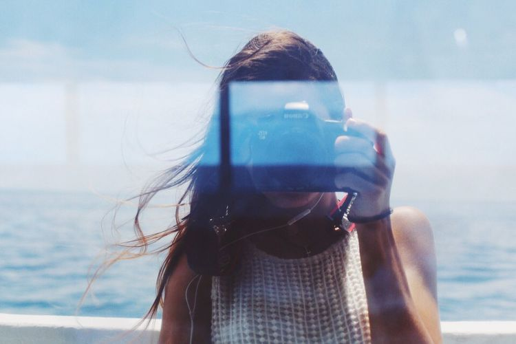 Close-up portrait of woman holding smart phone against sky