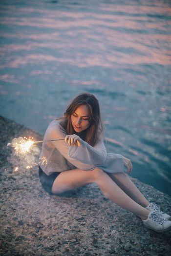 Woman with lit sparkler sitting against lake