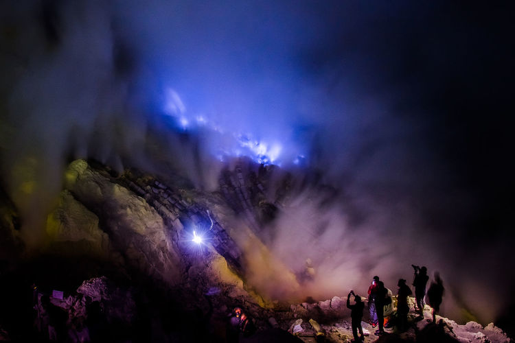 People on standing on mountain against sky at night