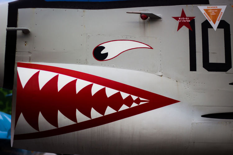Red Text No People Close-up Sign White Color Arrow Symbol Symbol Mode Of Transport Aeroplane Face Day Numbers Eyes Mouth Teeth Shape Star Shape Military Airplane