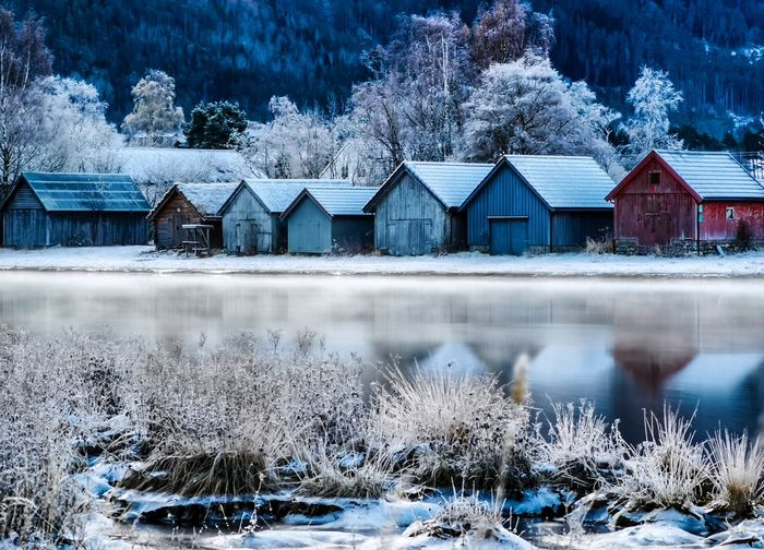 Houses by lake against buildings during winter
