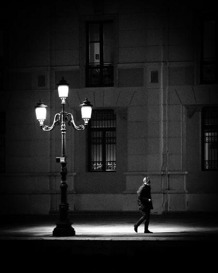 Full length of man walking on illuminated street against building at night