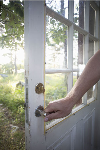 Midsection of man on door by window