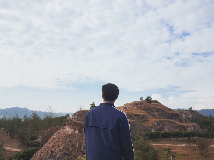 Rear view of man looking at mountains against sky