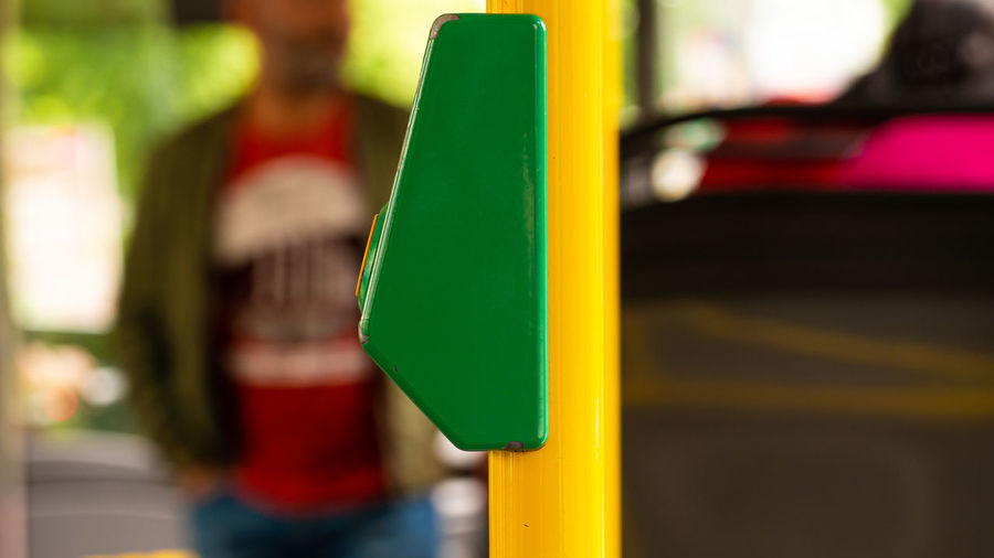 Close-up of yellow toy car on pole in city