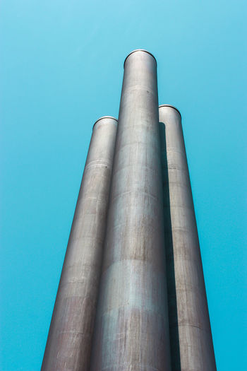 Air Pollution Architecture Blue Building Exterior Built Structure Chimney Clear Sky Day Factory Industry Low Angle View No People Outdoors Petrochemical Plant Pollution Sky Smoke Stack