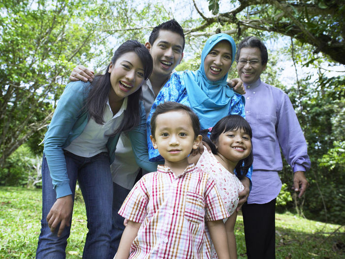 family taking family portrait at the park Asian  Family Fun Grandchildren Grass Happiness Holiday Innocence Mother Three Generations Cheerful Childhood Elementary Age Embracing Family Portrait Father & Son Forest Grandparents Leisure Activity Park Senior Smile Togetherness Tudung Vacation