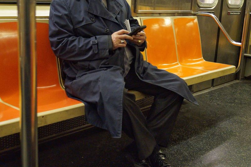 Midsection of man using mobile phone in train