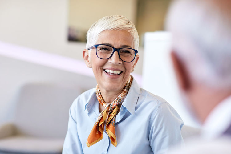 Happy woman looking at colleague in office
