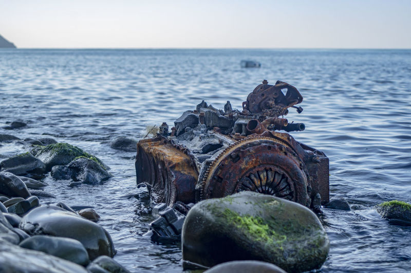 Old rusty engine lying among stones in the water.
