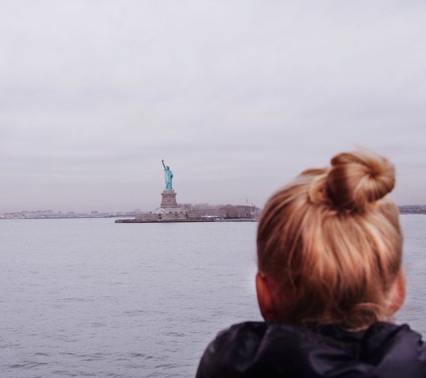 Rear view of woman sitting by sea looking at the statue of liberty