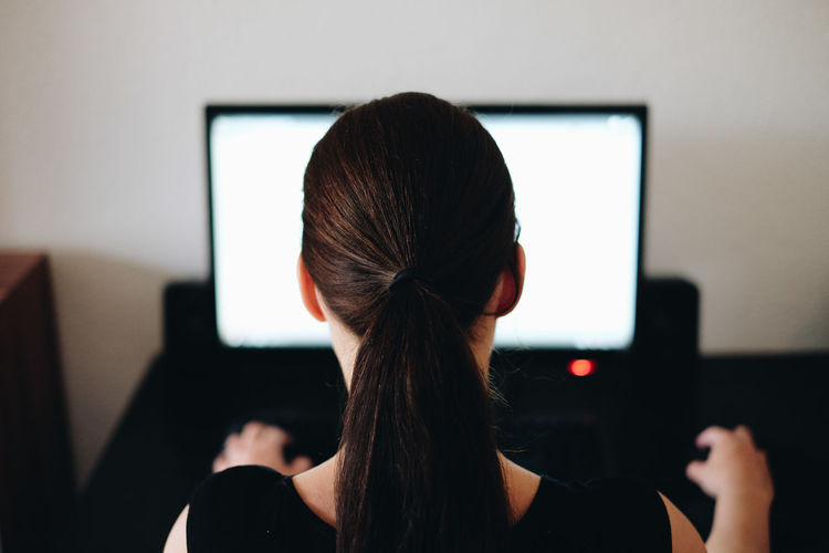 Rear view of woman working on computer at office