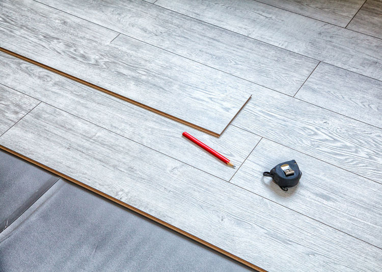 High angle view of pencil with tape measure on wooden table