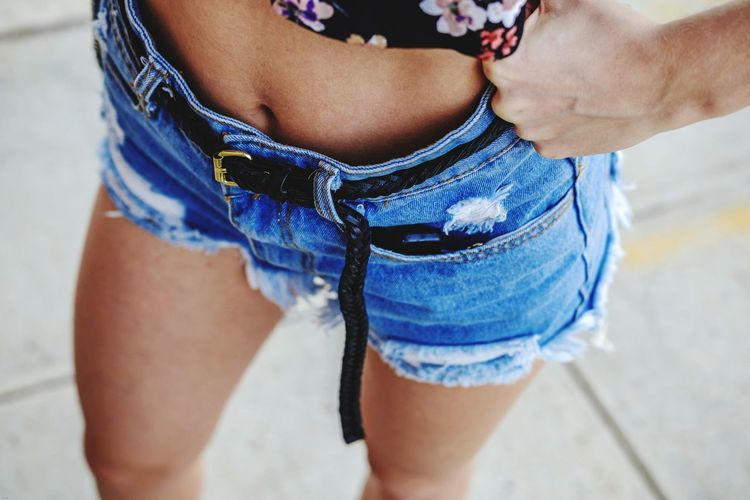 Midsection of woman wearing shorts while standing outdoors