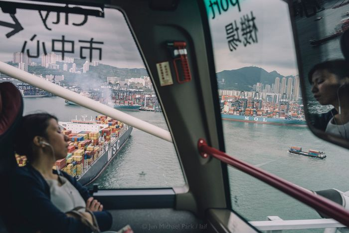 Container cargo ships and a sleeping passenger. May 2013, Hong Kong. HongKong Strangers In Transit Strangers ASIA Streetphotography Sony RX1 Travel Travel Photography Street Photography Cargo Ship Container City Urban Urban Geometry Fine Art Photography Jun Michael Park Laif Photo Agency Showcase July Reflection Mirror 35mm Urban Exploration