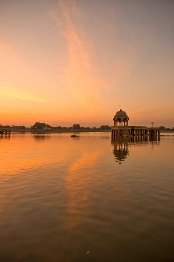 Sunrise over stone tower and historical building in Gadi Sagar lake, Jaisalmer, India. Architecture Beauty In Nature Building Building Exterior Built Structure Cloud - Sky Gadisagar Temple Gadisarlake Idyllic Jaisalmer Lake Nature No People Orange Color Outdoors Reflection Scenics - Nature Sky Sunset Tranquil Scene Tranquility Water Waterfront
