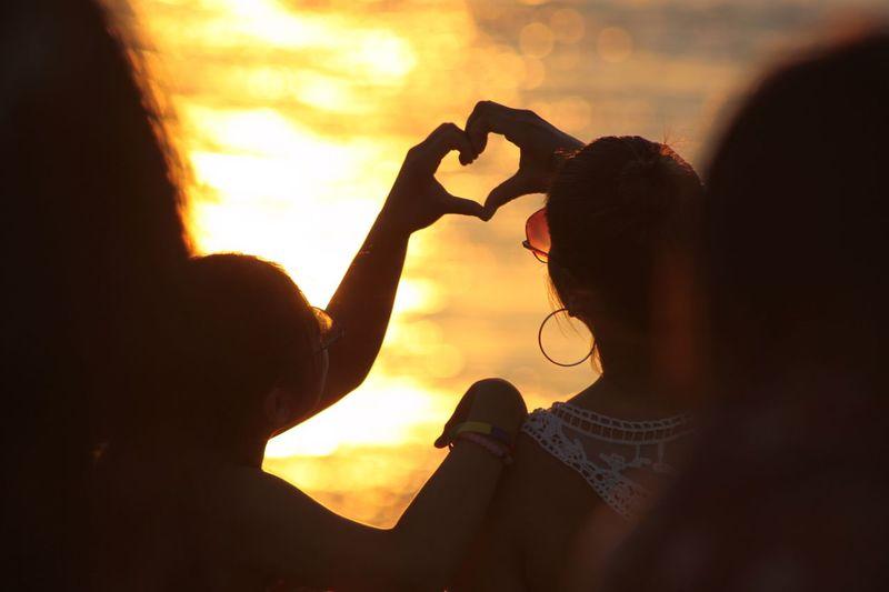 Women making a heart shape during sunset