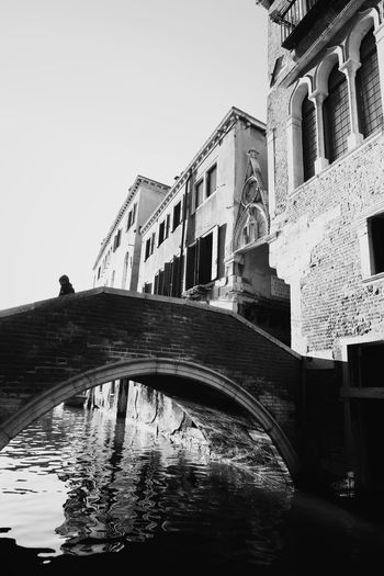 Low angle view of arch bridge over canal and buildings against sky