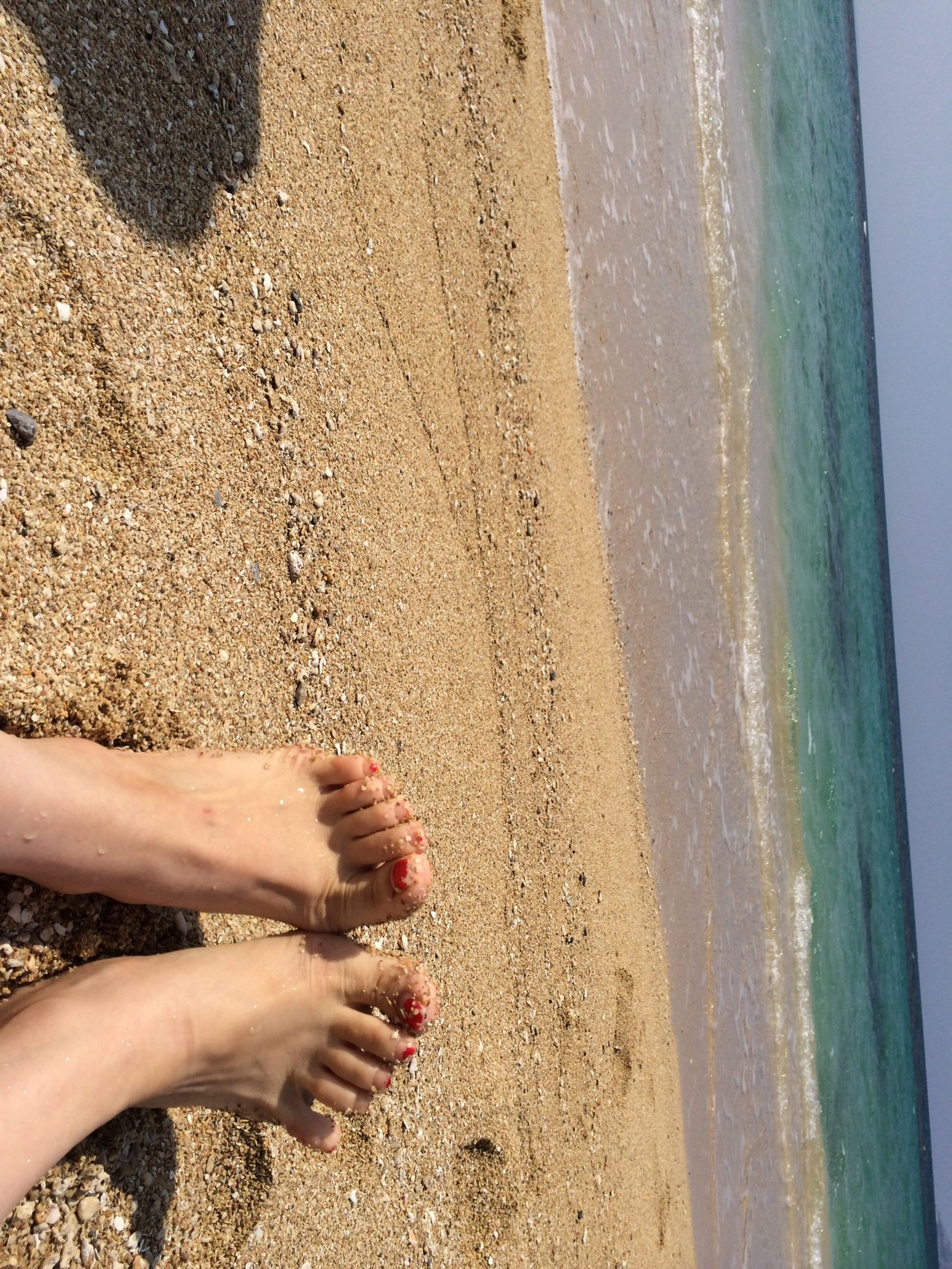 low section, lifestyles, person, beach, leisure activity, barefoot, sand, personal perspective, part of, human foot, sunlight, high angle view, day, outdoors, unrecognizable person