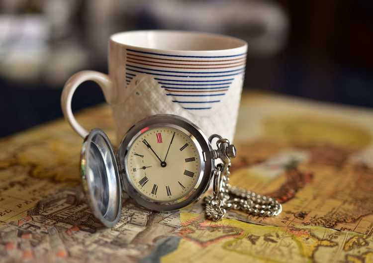 Close-up of pocket watch with cup on map at table