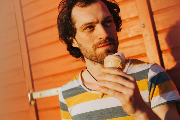 Close-Up Of Man Holding Ice Cream Cone Against Wall