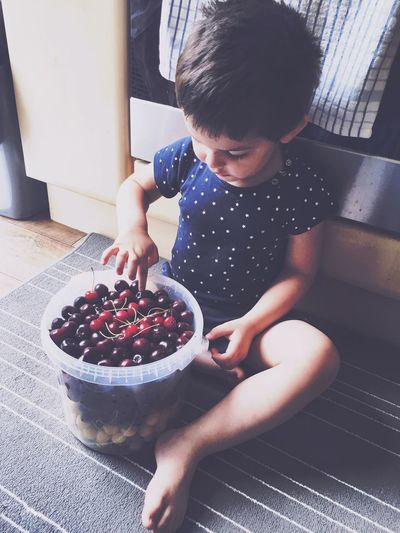 Childhood Real People Fruit One Person Casual Clothing Food And Drink Home Interior Indoors  Day Food Sitting Full Length Lifestyles Healthy Eating Freshness People Cherry Food Stories