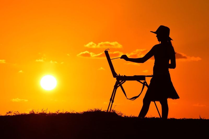 Silhouette Of Woman Painting A Picture At Sunset