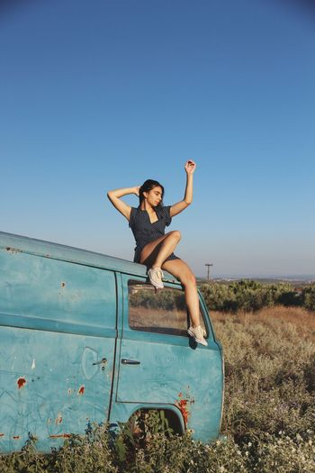 Young Woman With Arms Raised Sitting On Abandoned Van Against Clear Sky