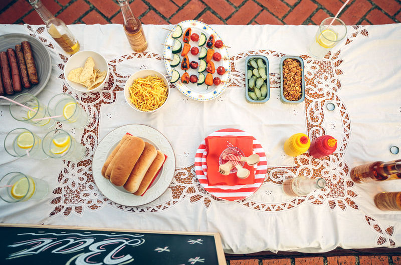 View from above of table with delicious food and drinks on tablecloth in a outdoors summer party BBQ Time Beer Food And Drink Friends Fun Horizontal Man Snack Woman Alcohol Barbecue Enjoy Garden Group Leisure Lifestyles Nobody Outdoors Party Sausage Summer Table Tablecloth Top View Vegetable