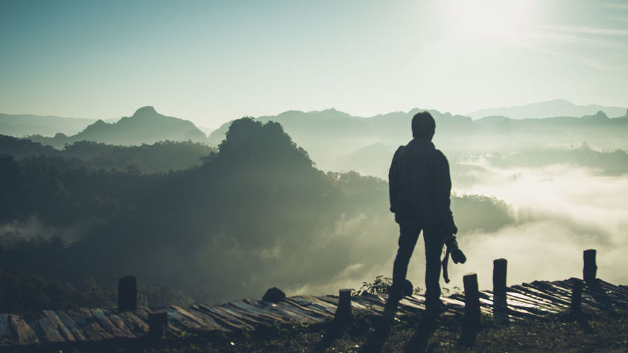 Man standing on boardwalk against mountains during foggy weather