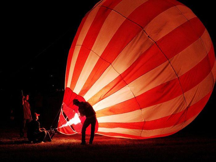People preparing hot air balloons at night